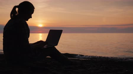 Side view of Silhouette of a woman working with a laptop by the sea at sunset
