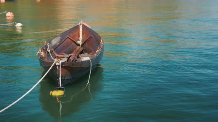 каноэ : A fishing boat is moored at the shore. Slowly swinging on a wave in a clear summer day Стоковые видеозаписи