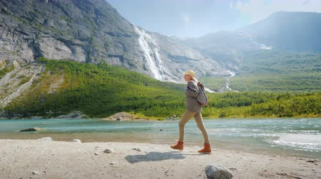 A traveler walks among the majestic nature - mountains and waterfalls. Picturesque places in Norway