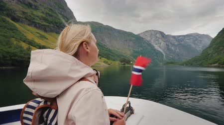 Active woman with the flag of Norway on the bow of the ship. Fjord cruises, trip to Scandinavia