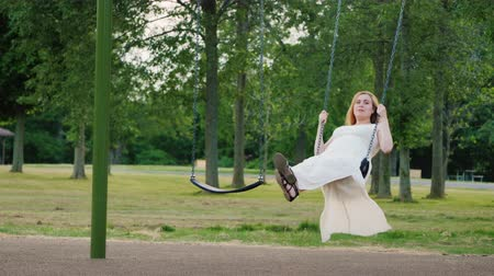 楽しんで : Young Caucasian pregnant woman rides a swing in the park