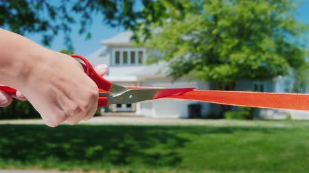 homeopático : A scissor-cut arm cuts a red ribbon, and a typical American house is visible in the background. Housewarming and buying a home concept Stock Footage