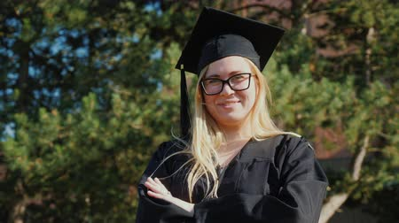 diploma : Portrait of a young college graduate in clothes and a graduation cap. Smiling, looking at the camera Stockvideo
