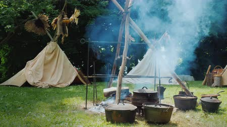 being prepared : Native American camp in the forest. Food is being prepared in the foreground, traditional wigwam tents are visible behind