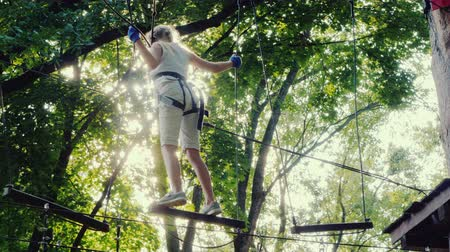 зажим : A brave child walks along a tightrope between tall trees. Active childhood and fun Стоковые видеозаписи