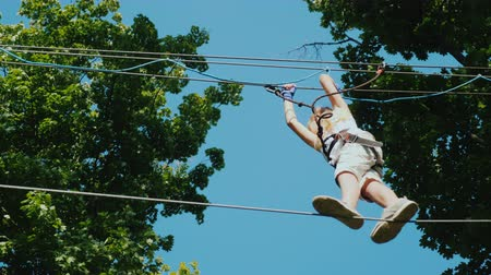 overcome : A brave child takes steps on a staggered cable at a height. Overcome fear concept Stock Footage
