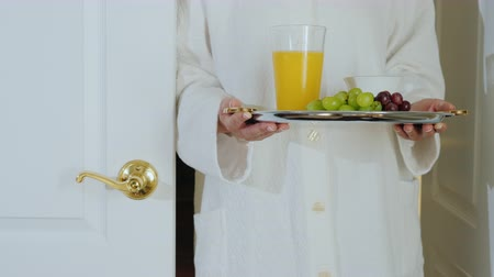 резидент : A woman in a bathrobe brings breakfast to the room. Romantic morning Стоковые видеозаписи