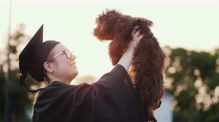 afstuderen : A young woman in a graduate costume holds a cute puppy in her arms. College Graduation Gift