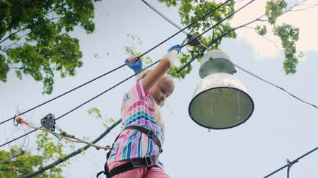 tightrope : Low angel view of A brave girl moves along the ropes between the trees, uses a safety rope Stock Footage