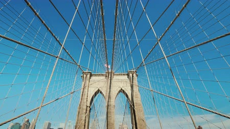 подвесной : Wide angle shot: Walk on the Brooklyn Bridge. Pylons and ropes of the bridge against the serene blue sky. Pov video Стоковые видеозаписи