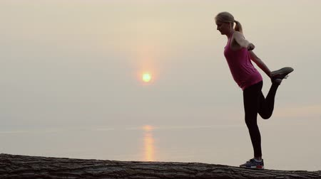 Active middle-aged woman doing stretching and balance exercise in a picturesque place by the sea