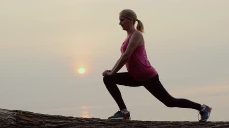 Active middle-aged woman is training against the backdrop of the sea and the rising sun