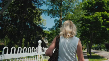 Young woman walking down the street in a typical American suburb, rear view