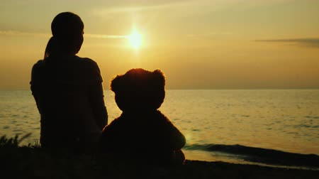 A lonely woman with a toy bear looks at the sunset over the sea. Sadness and loneliness concept