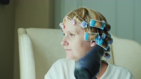 dryer : Woman with curlers on her head dries hair with a hairdryer