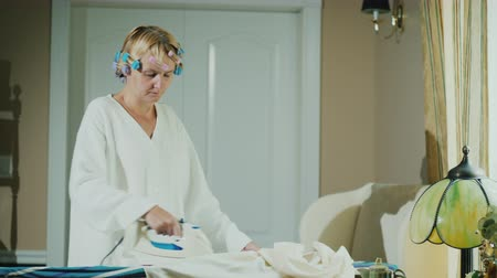 гладильный : Woman in a bathrobe with curlers on her head ironing clothes