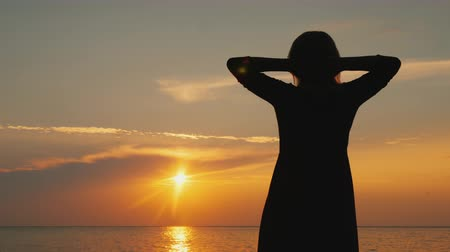 hayran olmak : A woman admires the beautiful sky where the sun sets, stands near the sea
