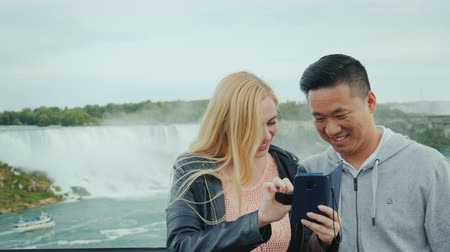 zuhatag : A young Asian guy and his Caucasian girlfriend are looking at a photo on a telphone on the observation deck of the Niagara Falls