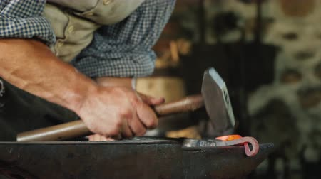 насилие : Hand of a blacksmith with a hammer, makes a forged product by striking the anvil. Antique crafts