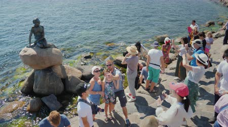 legendary : Copenhagen, Denmark, July 2018: Many tourists is photographed near the famous statue of the Little Mermaid in Copenhagen. Stock Footage
