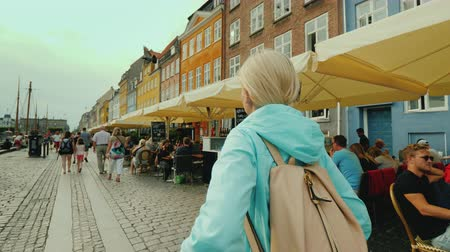 kopenhagen : Copenhagen, Denmark, July 2018: A woman strolls along the Nyhavn canal, against the background of famous colorful houses. The most popular place among tourists is in Copenhagen, Denmark