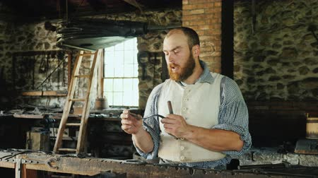 migrants : Genesee, NY, USA, July 2019: A blacksmith in traditional dress talks about his profession, is in an old blacksmith