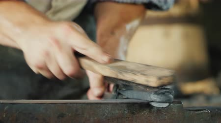 demirci : A blacksmith with a metal brush cleans the workpiece from scale and debris. Artisan craftsmanship