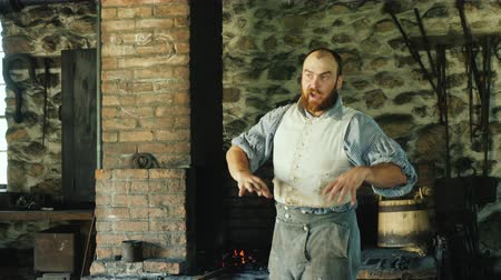 伝える : Genesee, NY, USA, July 2019: A blacksmith in antique clothing from the time of the development of America forges an iron product in a forge