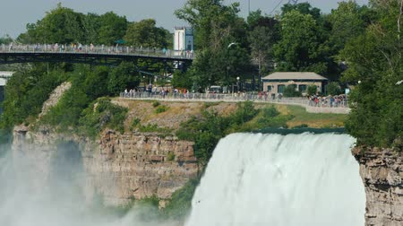 at nalı : A powerful stream of water in Niagara Falls, in the background in the background is a park where tourists walk