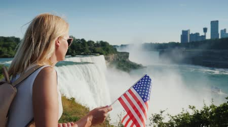 hayran olmak : Woman with USA flag admires view of Niagara Falls from American shore
