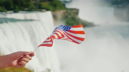 fer a cheval : Hand with USA flag on Niagara Falls background. Travel America