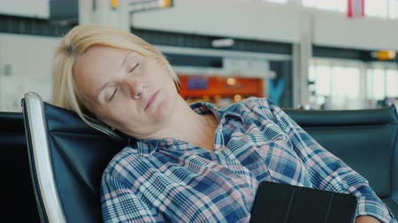 cancellation : Tired passenger sleeps in airport terminal while waiting for his flight