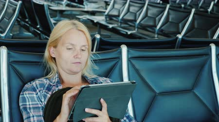 в ожидании : A woman uses a tablet in an airport lounge. Leisure pending flight
