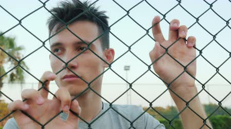 ninhada : Depressed teenager looks over the fence mesh Vídeos