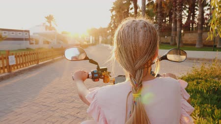 pigtailler : A child with African pigtails riding a scooter, rear view. Cheerful and active recreation