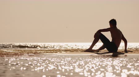 ninhada : Silhouette of a young man sitting on a small sand island Vídeos