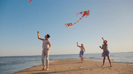 idílio : A young family actively spends time together - they play kites