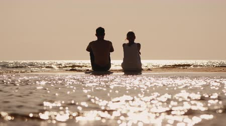 близость : A young couple sits on a sandy island and looks forward to the horizon