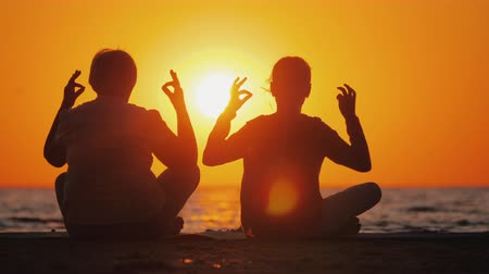 zen como : Grandmother and granddaughter meditate on the beach. Active and healthy seniors concept
