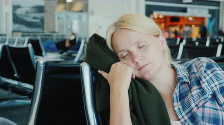 opheffing : A young woman fell asleep in the airport terminal. Flight delay or cancellation concept