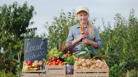 patlıcan : Little farmer girl at the counter with vegetables, holding a carrot Stok Video