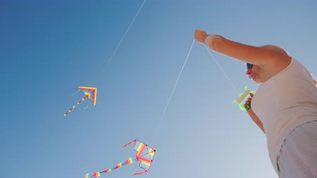 Active rest on the beach - woman playing with kite, low angle shot