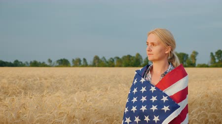 hayran olmak : Woman farmer with usa flag on weeds walking along wheat field Stok Video
