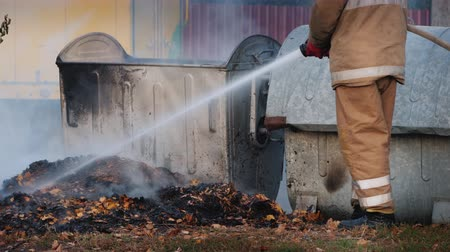 prullenbak : Firefighter puts out a fire near garbage bins after a riot