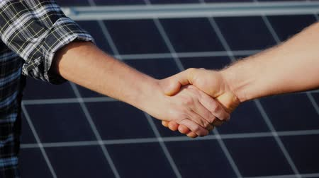 small businessman : Handshake of two businessmen on a background surface of solar panels