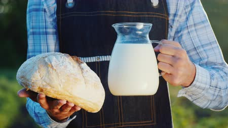 korsó : A man holds a jug of milk and a loaf of bread