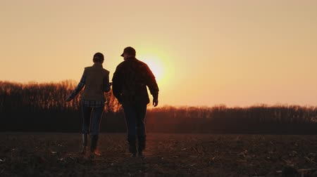 agronomist : Man and woman farmers go on a plowed field at sunset.