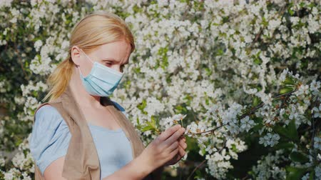 irritatie : A woman in a gauze bandage examines a flower against a blossoming tree. Allergic Disease Problems