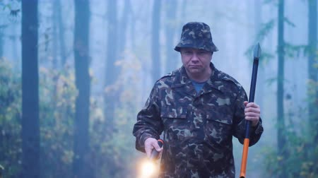 топор : Brutal man with an ax and a flashlight walks through the forest Стоковые видеозаписи