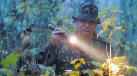 lanterna : A man shines a flashlight at dusk in the forest. Search operation